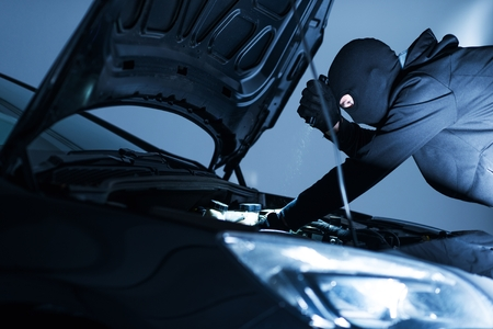 disarm: Robber Disabling Car Alarm. Car Robber Looking To Disarm Car Security Systems Under the Car Hood. Stock Photo