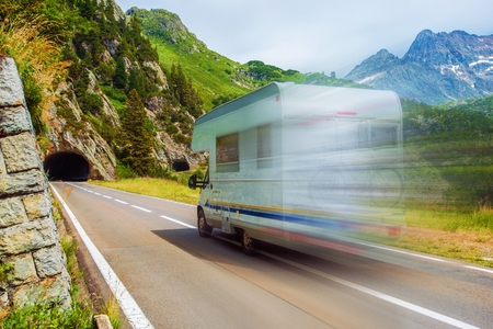recreational vehicle: Speeding Camper on a Mountain Road. Class C Recreational Vehicle. Vacation Adventures. Stock Photo