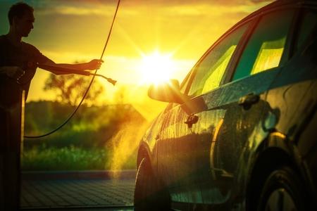 Spring Car Washing During Sunset. High Pressure Water Washing System. Stock Photo