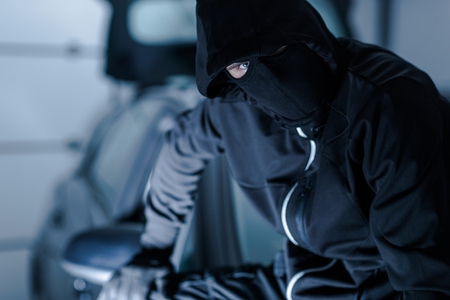 car theft: Car Theft Portrait. Successful Theft in Black Face Mask Seating on a Freshly Stolen Car.