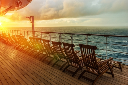 Cruise Ship Wooden Deck Chairs. Cruise Ship Main Deck at Sunset. 스톡 콘텐츠