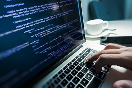 tecnologia: Programmazione Tempo di lavoro. Programmer Digitando Nuove linee di codice HTML. Portatile e la mano del primo piano. Orario di lavoro. Web Business Design Concept.