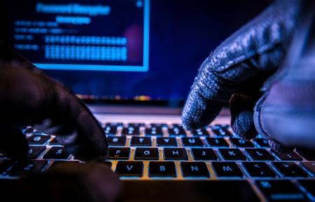 teclado: Los pagos de Hacking sistema. Tarjetas de crédito en línea Concepto de Seguridad de los pagos. Hacker en guantes negros pirateo del sistema.