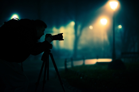 photography: Photographer Taking Pictures at Night in the Foggy Park. Photography Hobby Stock Photo