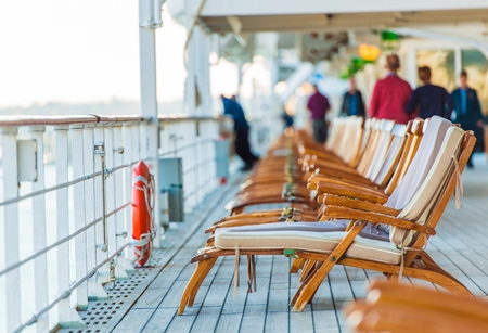 convés: Navio de cruzeiros cadeiras de madeira e alguns turistas idosos.