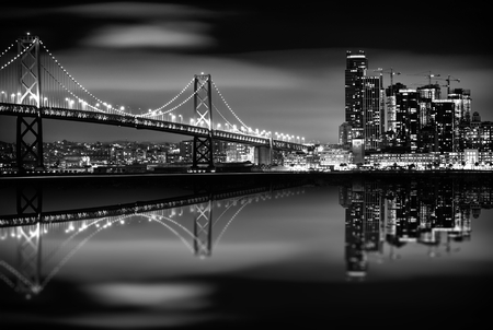 the bay: The San Francisco Bay at Night in Black and White. Bay Bridge and San Francisco Skyline. Monochrome.