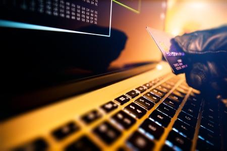 소유자 허가없이 온라인으로 카드를 사용하려고하는 도둑의 손에 신용 카드를 도난당했습니다. 온라인 지불 보안 및 신분 도용 개념 사진입니다.