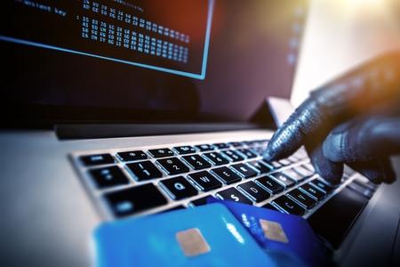 ladron: Tarjetas de crédito Robo Concepto. Hacker con tarjetas de crédito en su computadora portátil usarlos para compras no autorizadas. Los pagos no autorizados