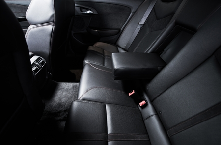 back seat: Back Seat Car Travel. Modern Comfortable Black Leather Seats Inside New Car. Stock Photo
