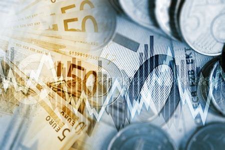 stock trading: European Economy Concept. Euro Currency Fifty Euros Banknotes and Euro Cent Coins with Some Line Graphs.