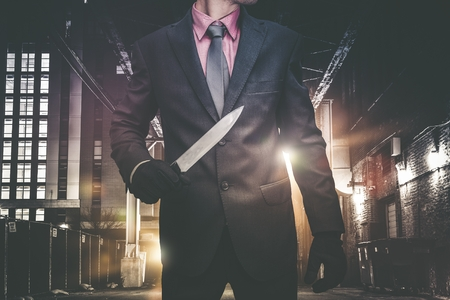 thriller: Psychopathic Downtown Murderer Walking Through the Alley with Huge Knife. Wearing Elegant Suit and Tie. Urban Crime Concept.