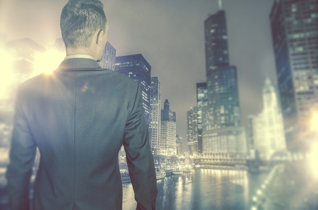 ambitious: Business in the City Concept. Young Ambitious Businessman in Front of Large City with Skyscrapers.