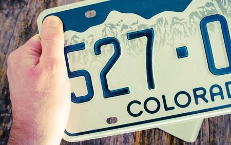 Nummerplaat van Colorado in de hand close-up foto. Colorado Vehicle Licensing. Stockfoto
