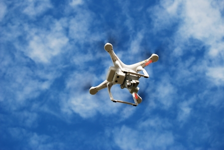 computerized: Flying Small Toy Drone on the Cloudy Sky. Drone Technology.