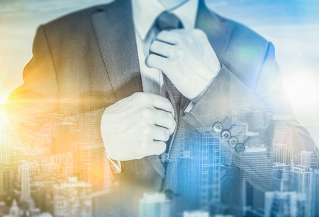 suite: The Business Plan. Young Strong Minded Mastermind Businessman Wearing His Suite in Front of the Window with Cityscape Reflection. The Men with Business Idea. Stock Photo