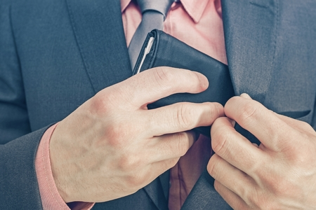 hidden taxes: Businessman and His Wallet. Businessman Reaching For His Wallet to Pay. Closeup Photo.