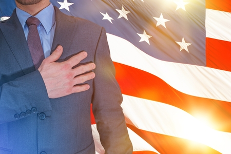 Patriota americano orgulloso manteniendo su mano en un corazón. Patriota con la bandera americana en un fondo. Nosotros, las personas.