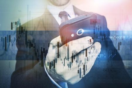 モバイル ビジネスの概念を投資します。彼のモバイル デバイスを使用して株取引の実業家。スマート フォンでリモートで作業の男性。