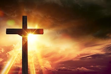 Velký dřevěný kříž při západu slunce s zprava kopií vesmíru.