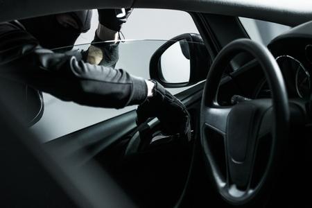 robo de autos: Ladrón de coches intentando abrir coche Desde el Interior