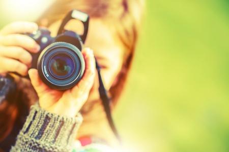 season photos: Girl with Modern Digital Interchangeable Lenses Photo Camera.