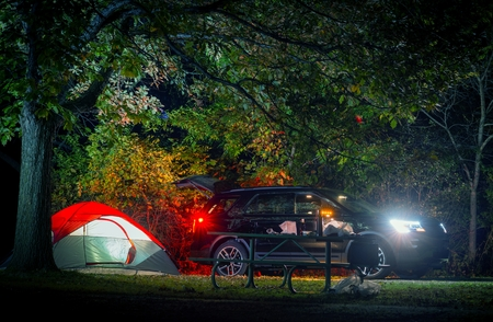 sport utility vehicle: Summer Overnight Tent Camping. Modern Sport Utility Vehicle and Illuminated Small Double Tent Under Old Tree.
