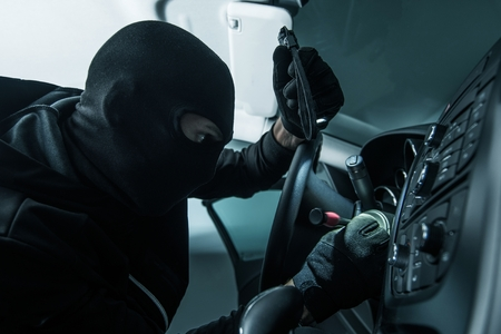Caucasian Car Thief in Black Mask. Stock Photo