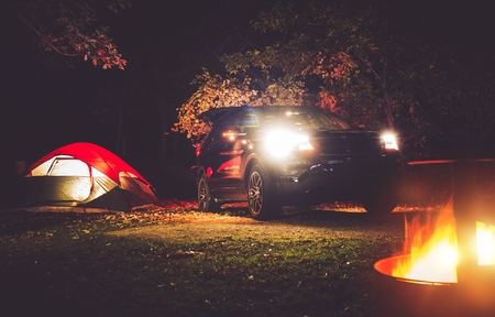 Tent Camping in the Deep Forest. Modern Off road Car, Tent and Burning Wood in the Camping Fire Pit. Stock Photo