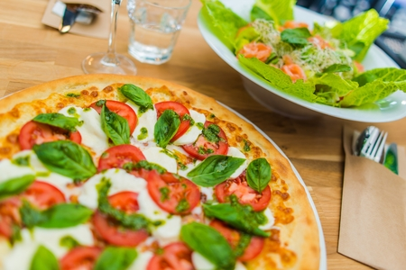 sandwitch: Fresh Tomato and Basil Margarita Wood Fired Oven Pizza and Salmon Salad on Wooden Table.