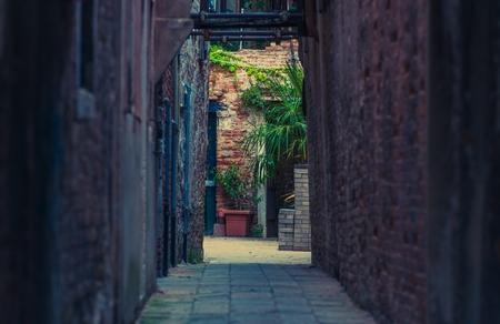 italian architecture: Narrow Italian Sidewalk Between Old Buildings. Venetian Architecture Theme. Stock Photo