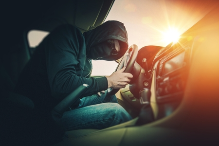 rubbery: Car Thief in a Black Mask and Black Glasses Inside the Modern Car.