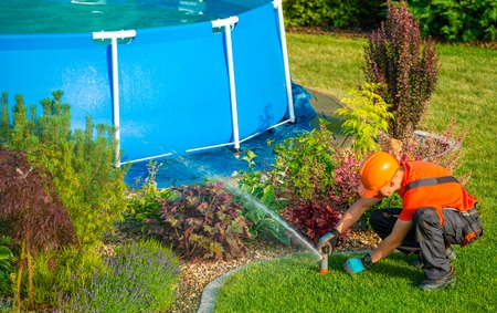 sprinkler: Caucasian Lawn Garden Technician in the Residential Garden with Swimming Pool Taking Care of Lawn Sprinklers System. Stock Photo