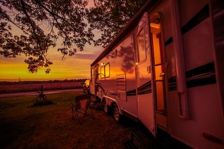 Travel Trailer Camping Spot na Scenic západu slunce. Tahání Travel Trailer autem. Reklamní fotografie