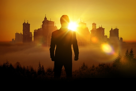 Corporations: Entrepreneur Vision Concept. Powerful Entrepreneur Businessman in Front of the City. Creating Powerful Corporation Concept. Men in Front of the City Skyline Covered By Clouds During Sunset.