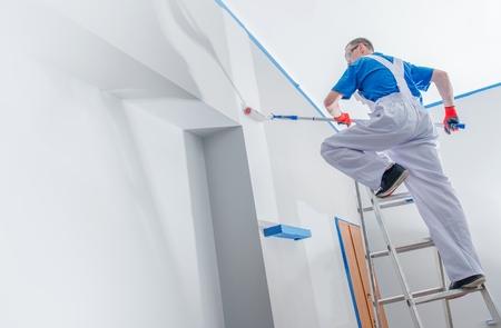 Haus Malerei und Renovierung Business-Konzept. Kaukasischer Mann Malerei Haus Zimmer von der Leiter. Standard-Bild - 56892183