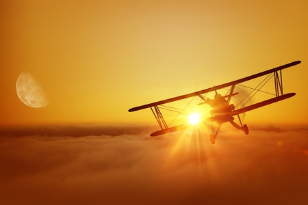 日没時に雲の上の飛行機。偉大なる飛行機飛行の冒険。複葉機の飛行。 写真素材