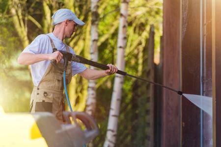 gospodarstwo domowe: Spring Time Dom Ściany czyszczące przez Wysokie ciśnienie wody rozpylanie. Kaukaski mężczyzn w miejscu pracy.