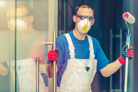 Professional Office Painting Service. Caucasian Male with Painting Roller Preparing for Office Painting. Office Renovation. Professional Painter.