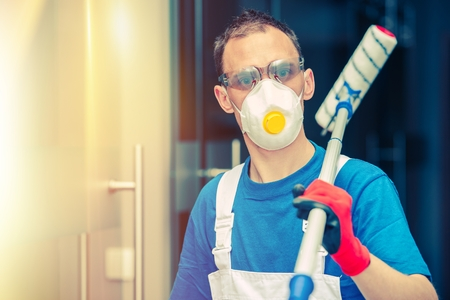 safety mask: Pro House Painting. Professional House Painter with Painting Roller, Safety Mask and Glasses. Indoor Painting.