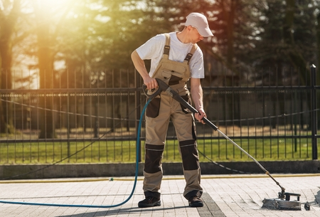 Brick Residential Rijweg Schoonmaken bij Professional Cleaning Worker. High Pressure Water Mechanische Brick en trottoirs Cleaning Service Theme.
