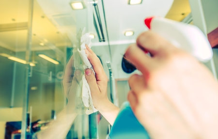 Office Windows Cleaning. Male Worker Cleaning Glass Walls in the Office Area. Cleaning Service. 스톡 콘텐츠