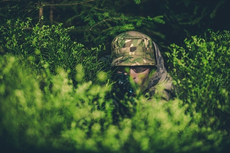 Camouflaged Poacher with Rifle at Hunt in the Dense Forest.