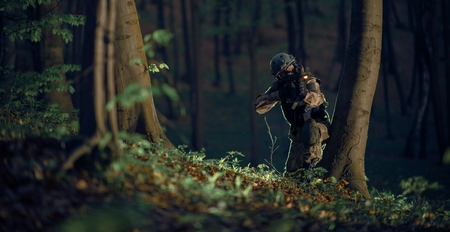Military Soldier in Action at Night in the Forest Area. Night Time Military Mission. Panoramic Photo. Soldier with Assault Rifle with Flashlight Between Trees. Banco de Imagens - 56892236