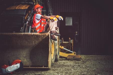 Der Mensch und die Maschine. Bulldozer und Bagger Operator Pause bei der Arbeit. Professionelle Europäischer Baumaschinen Betreiber.