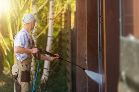 차고 문 물 청소. 차고 벽과 문 강력한 고압 물 세척. 백인 노동자 청소 건물 요소.