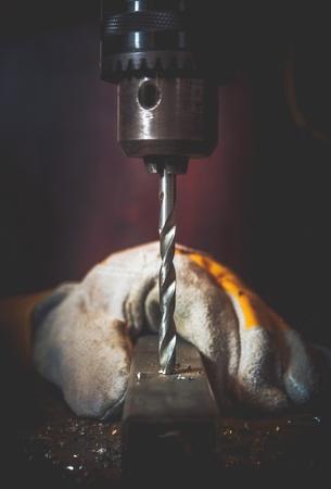 Metal Drilling Works Closeup Photo. Vertical Rotating Drill Bit Closeup.
