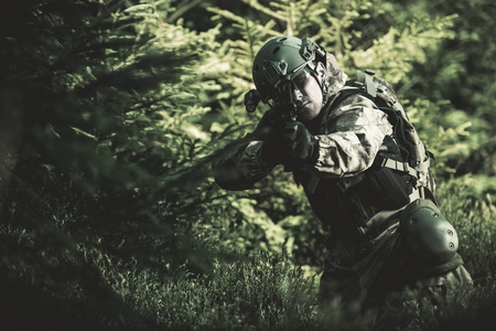 assault rifle: Special Forces Soldier. Camouflaged Marine Soldier Shooting Assault Rifle. Army Military Mission Concept Photo.