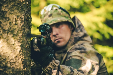 poacher: Wildlife Hunter with Rifle Spotting Deer. Hunter Poacher Concept Photo.