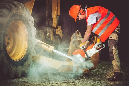 cutter: Construction Worker in Action. Worker Cutting Concrete by Using Heavy Duty Electric Cutter. Construction Site. Stock Photo
