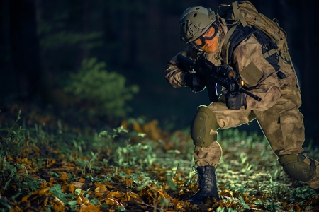 troop: Night Time Special Operation. Running Troop Soldier with Assault Rifle at Night in the Forest. Stock Photo